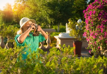 Senior woman with camera. Lady standing near plants. Photographer in botanical garden. Inspiration and mood.