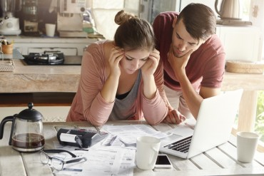 Stressed young Caucasian couple facing financial problems, not able to pay off their loan because of many debts. Woman with headache and worried man feeling stress, reading notification from bank