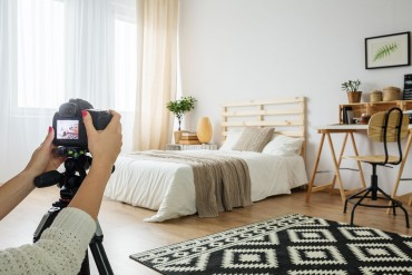 Blogger taking a photo of a modern bedroom