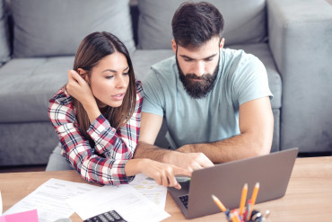 Worried couple checking their bills at home