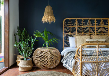 Traditional asian bedroom with ethnic decor, lamp over nightstand table, comfortable bed, carpet or rug, exotical cactus in basket and natural green plant composition. Conceopt of cozy house interior