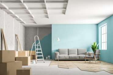 Blue living room interior with a gray sofa during renovation process. Unfinished floor, boxes and a ladder in the corner. 3d rendering mock up